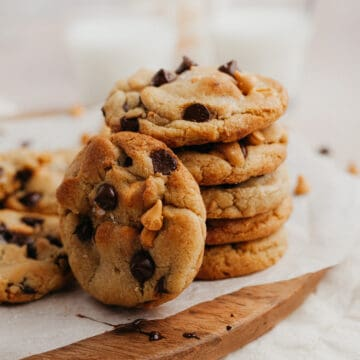 a stack of butterscotch chocolate chip cookies on a wooden board