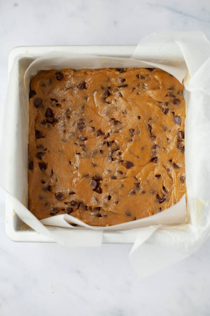 A square baking pan with unbaked cookie butter blondies