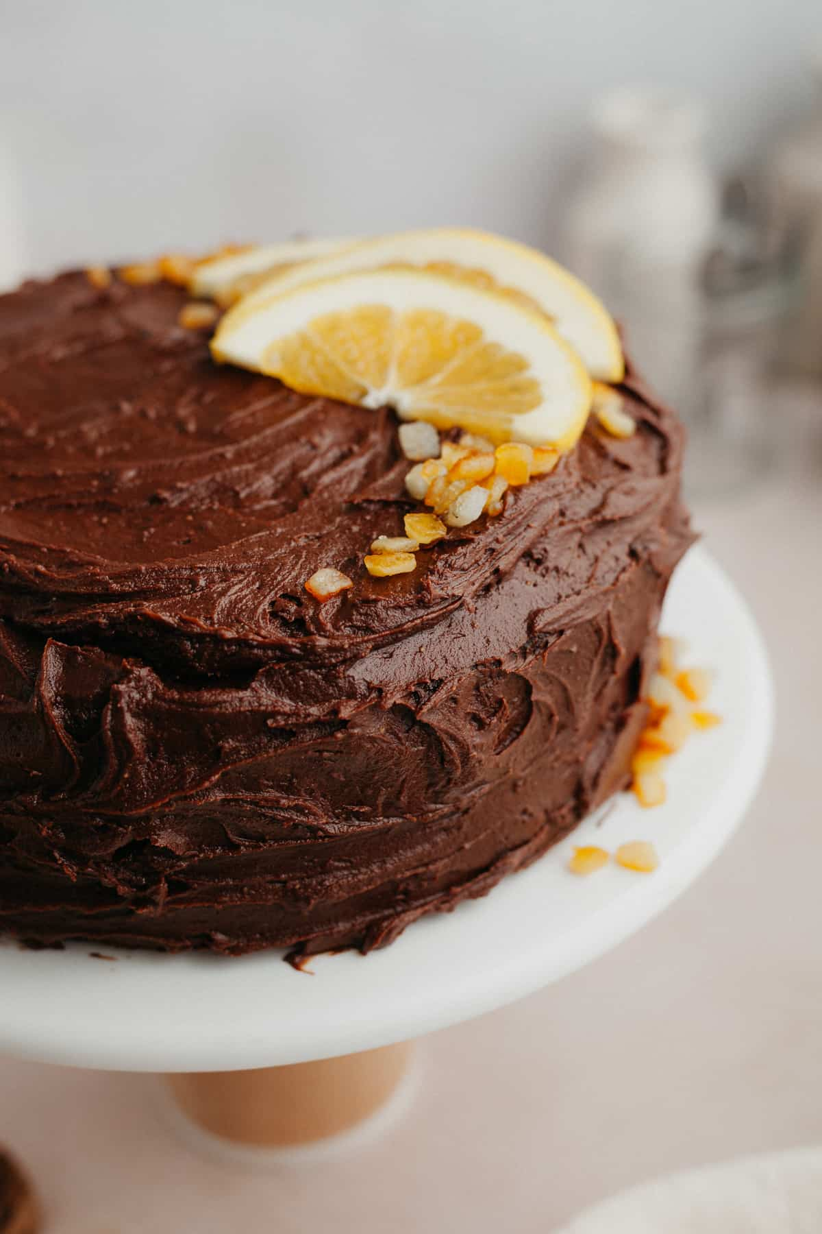 Side angle view of a chocolate orange cake, frosted with chocolate frosting and the top has sliced oranges