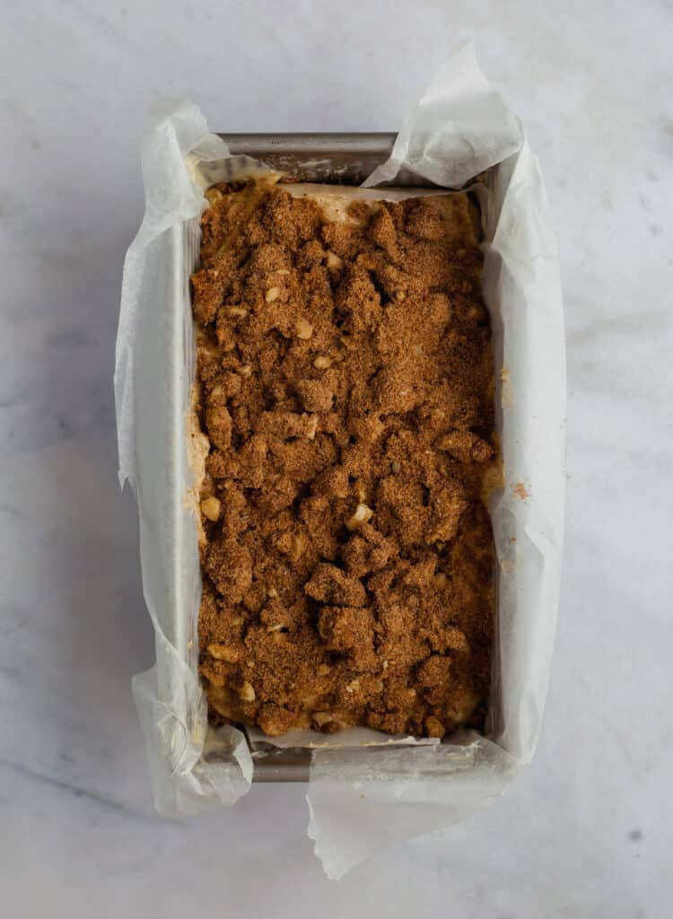 Unbaked banana bread covered in cinnamon crunch topping