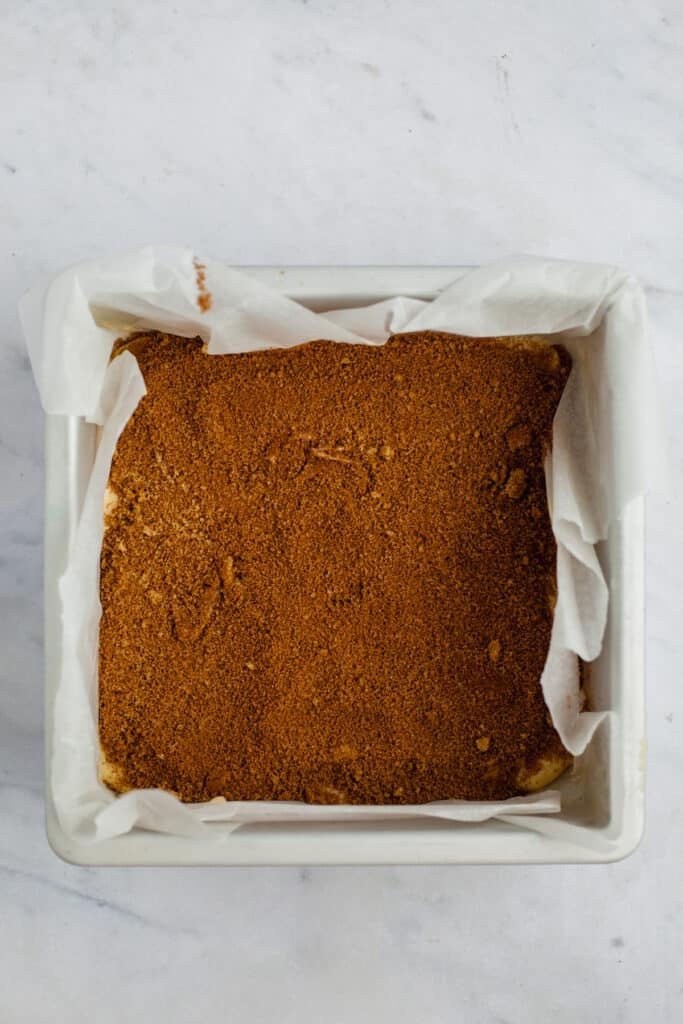 A square baking pan with coffee cake batter and streusel