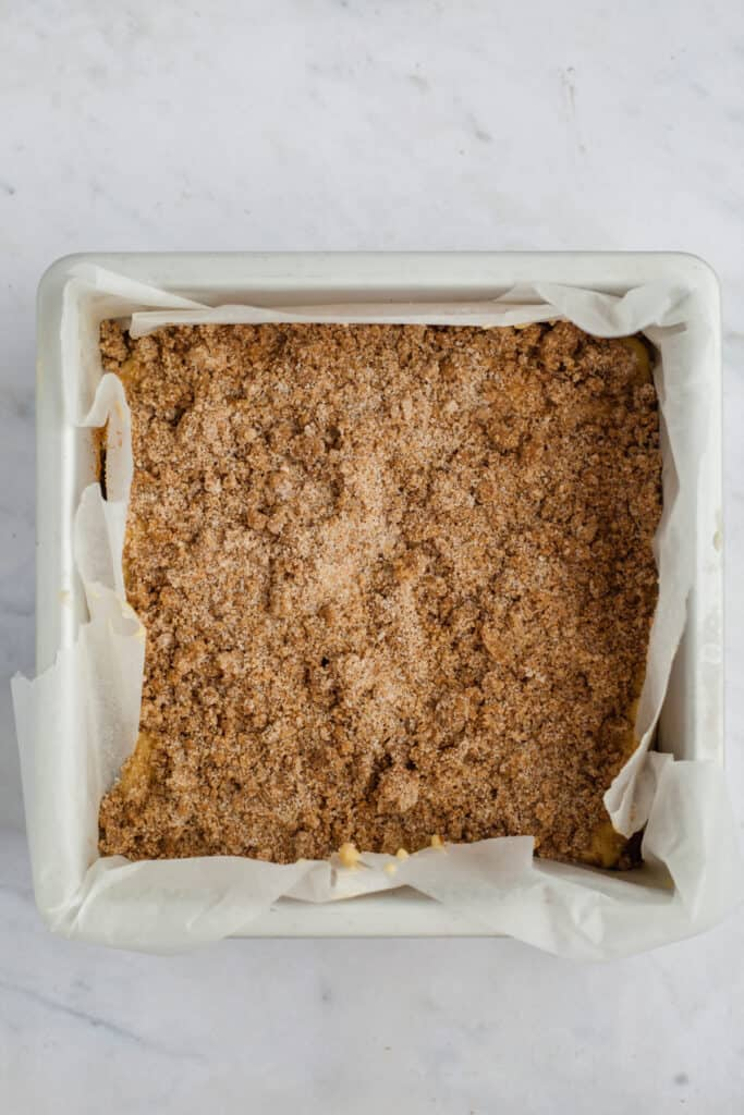 A square baking pan with cake batter and cinnamon filling