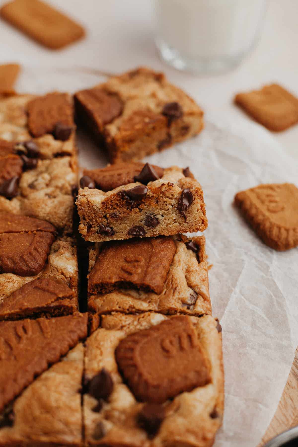 chocolate chip cookie butter blondies slices on parchment paper. One has been angled upwards so you can see a cross section of the bar.