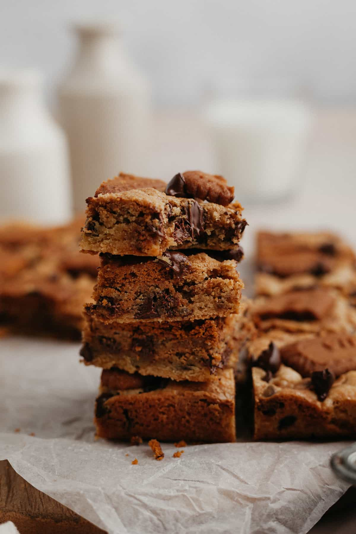 A stack of 4 cookie butter blondies on parchment paper