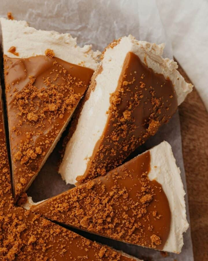 Three slices of biscoff cheesecake on a wooden circular board