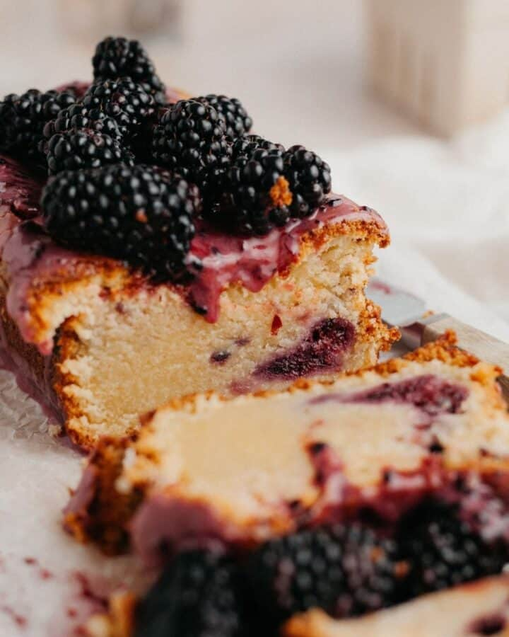 A blackberry lemon bread loaf covered in a purple glaze and blackberries. Several slices have been cut off.
