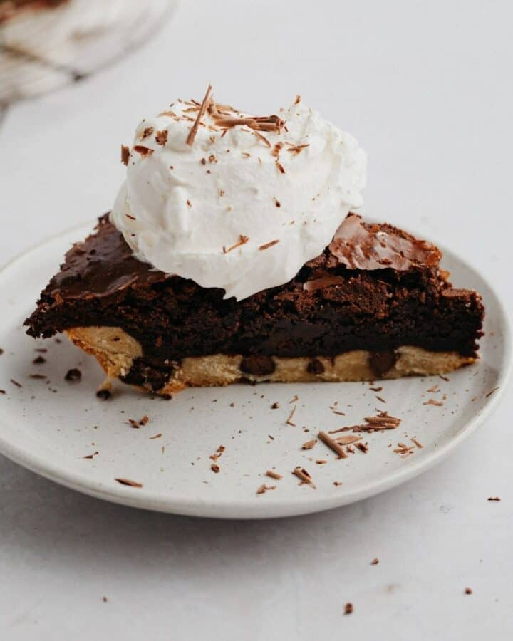 A slice of brownie pie with a dollop of whipped cream