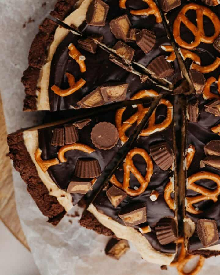 An overhead shot of peanut butter cup pie covered in peanut butter cups and pretzels.
