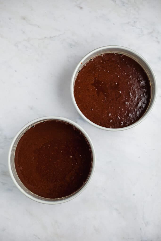 Two cake pans with unbaked chocolate cake
