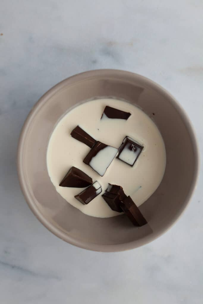 A grey bowl with chocolate and cream