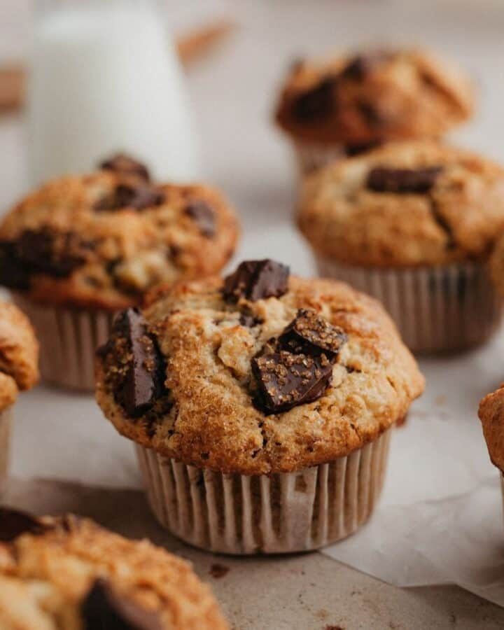 Peanut butter muffins with chocolate chunks on parchment paper