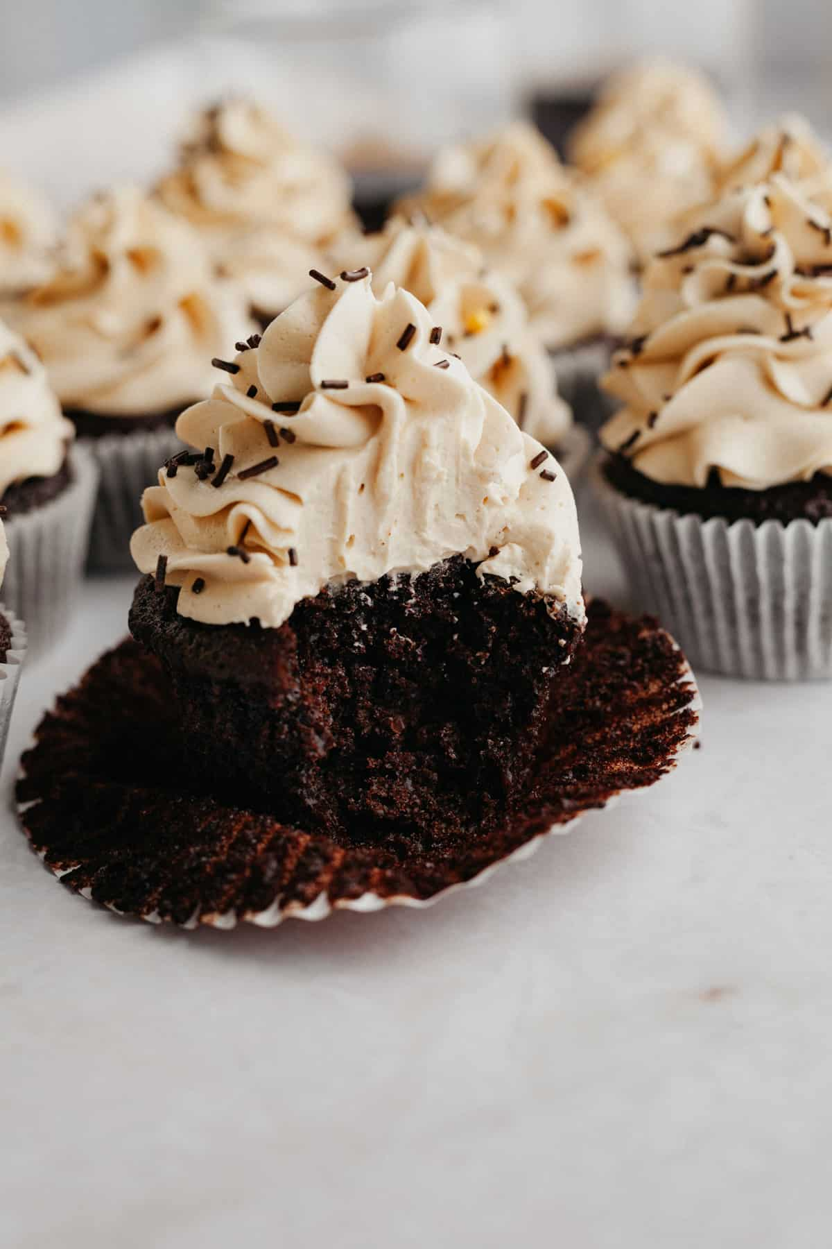 A mocha cupcake with a bite taken out of it