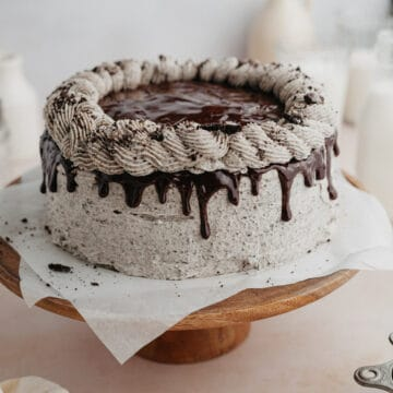 An oreo drip cake on a wooden cake stand