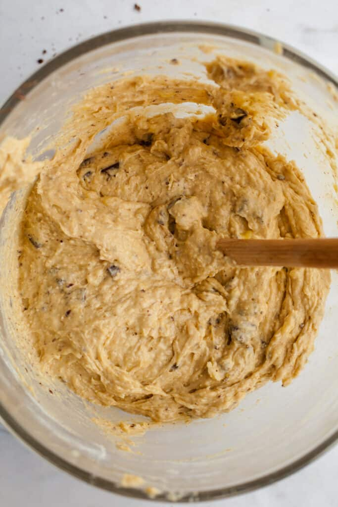 A glass mixing bowl with peanut butter banana muffin batter