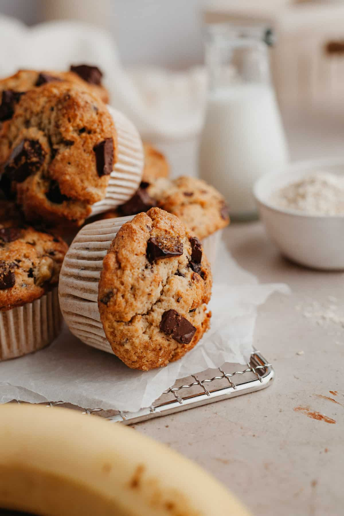 chocolate chunk muffins piled up together on a wire cooling rack