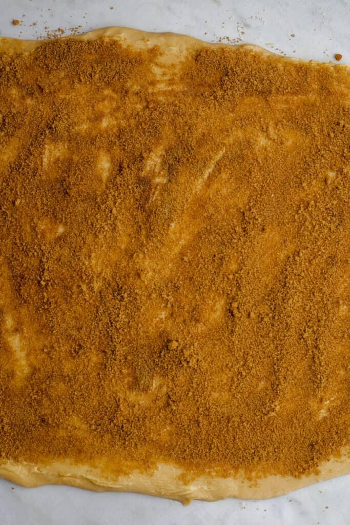 Rolled out cinnamon bun dough covered in cinnamon sugar