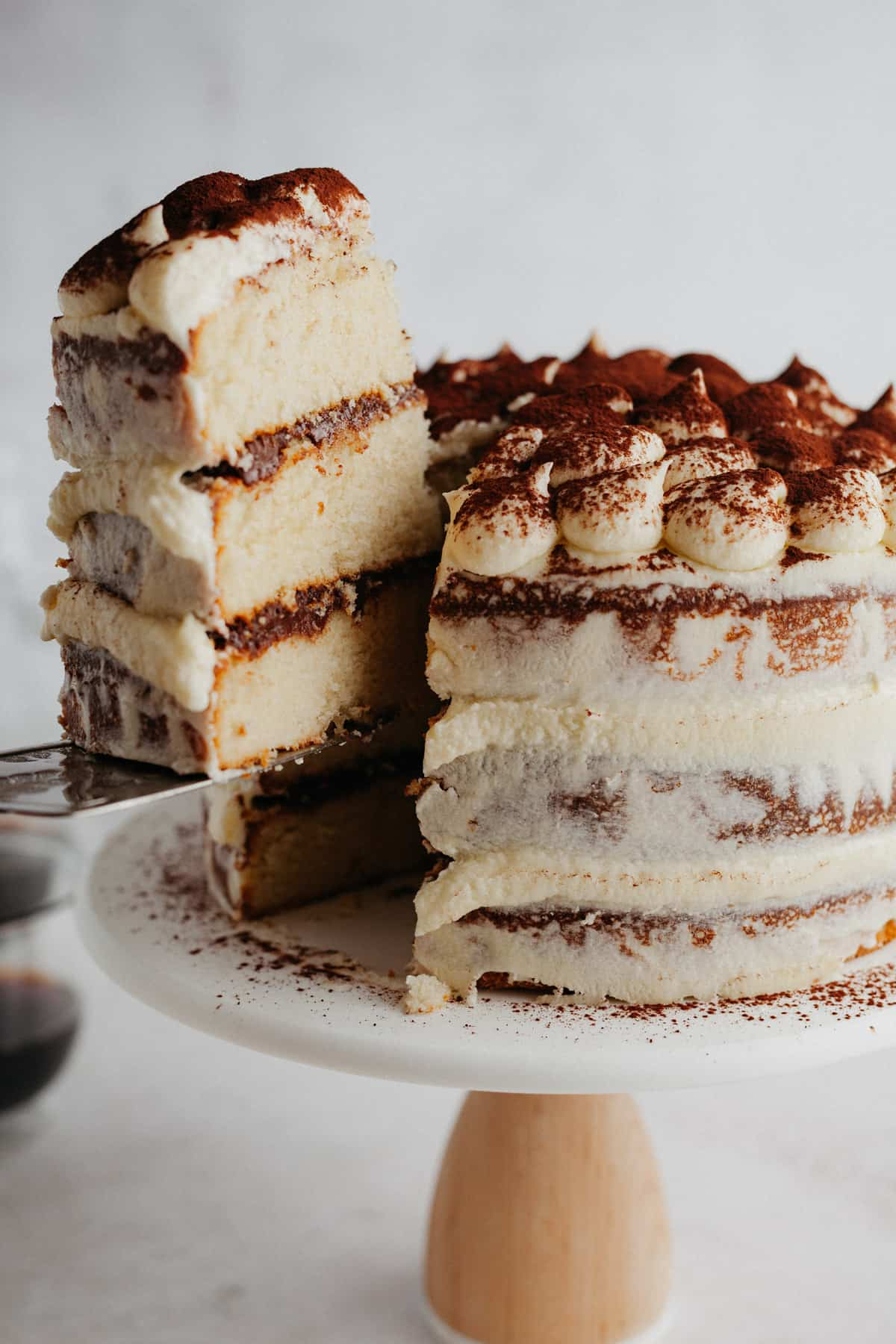 Tiramisu layer cake on a cake stand, one slice is being lifted out