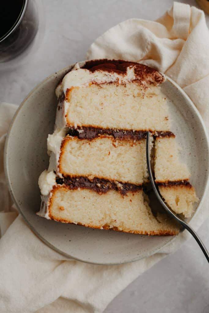 A slice of tiramisu cake on a small beige plate