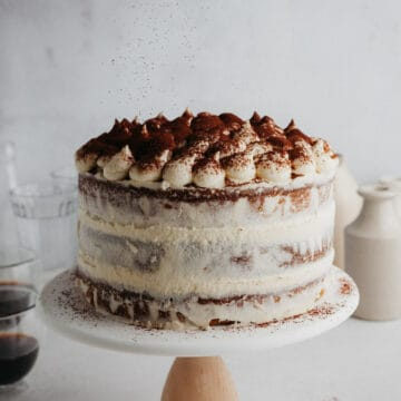 A tiramisu layer cake on a white cake stand
