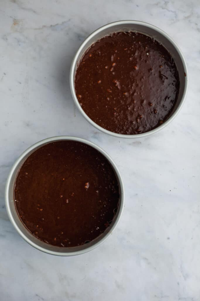 two cake pans with unbaked chocolate cakes