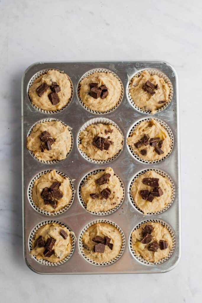 A muffin tray filled with unbaked peanut butter banan amuffin batter