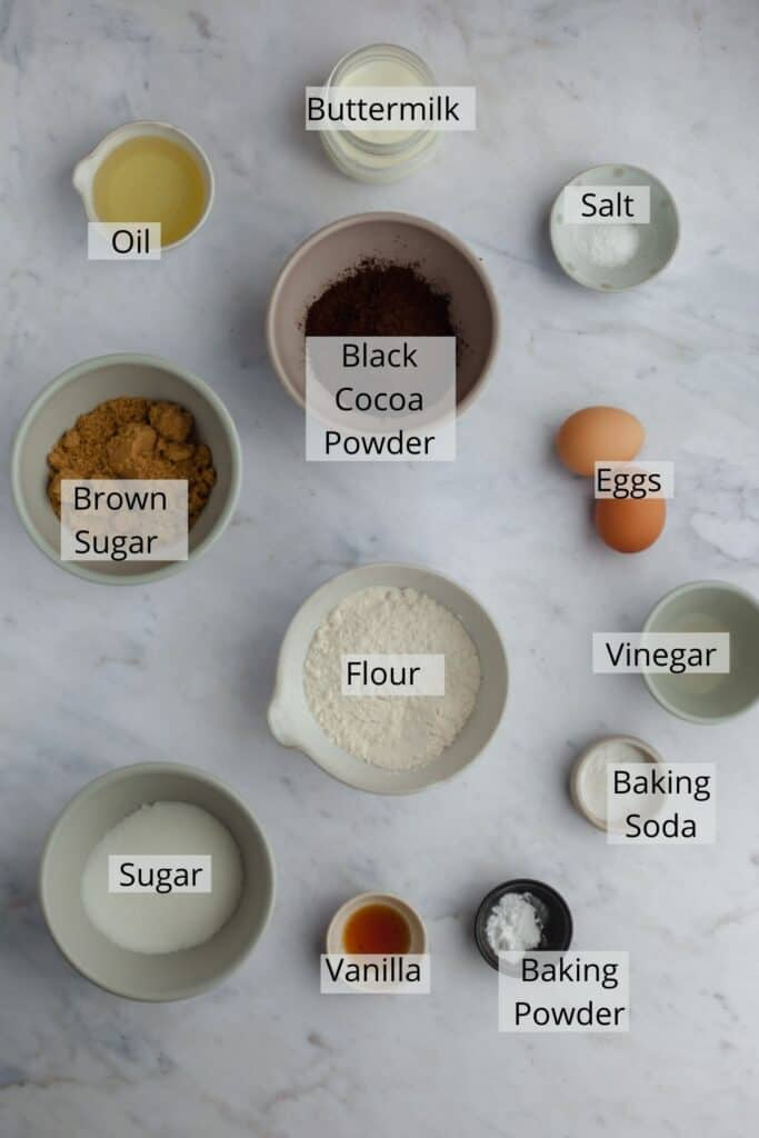 ingredients for black velvet cupcakes measured out in small bowls, like flour and cocoa powder.