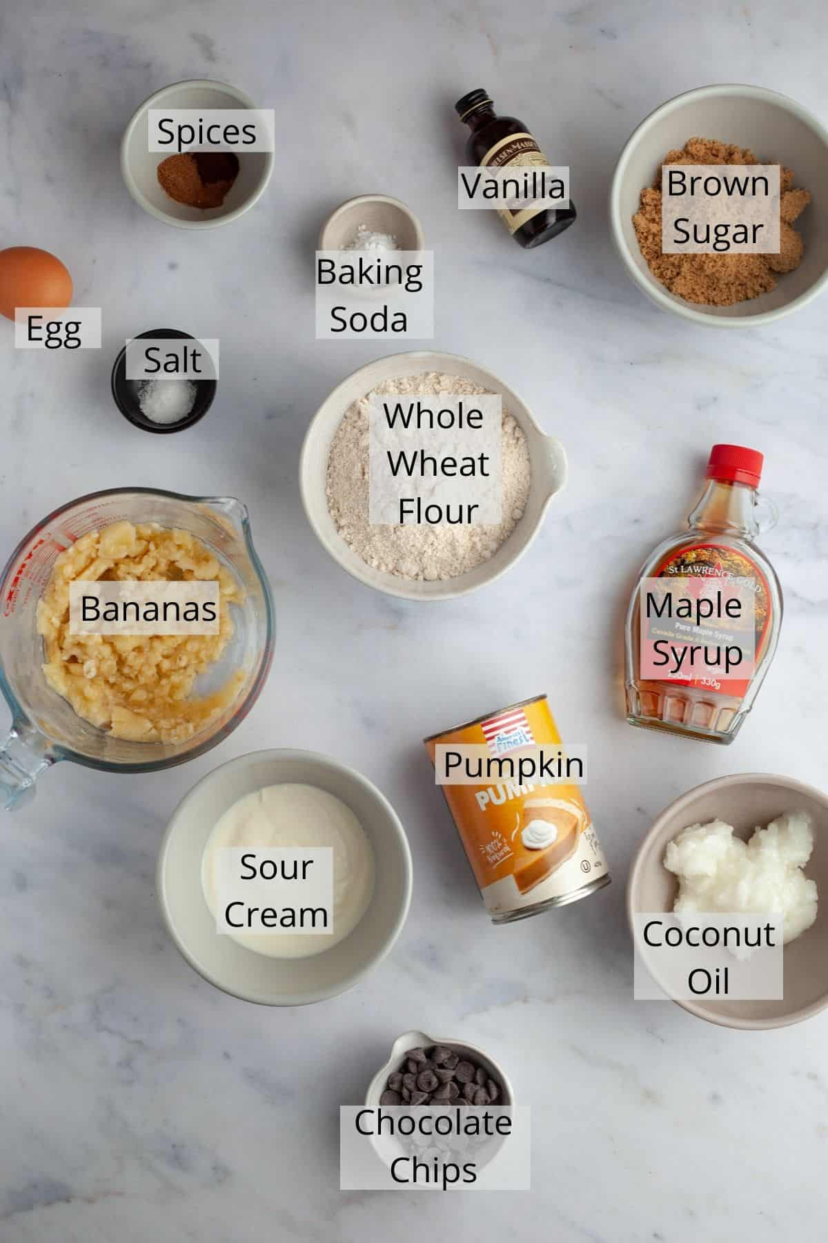 ingredients for pumpkin banana bread measured out in a variety of small bowls
