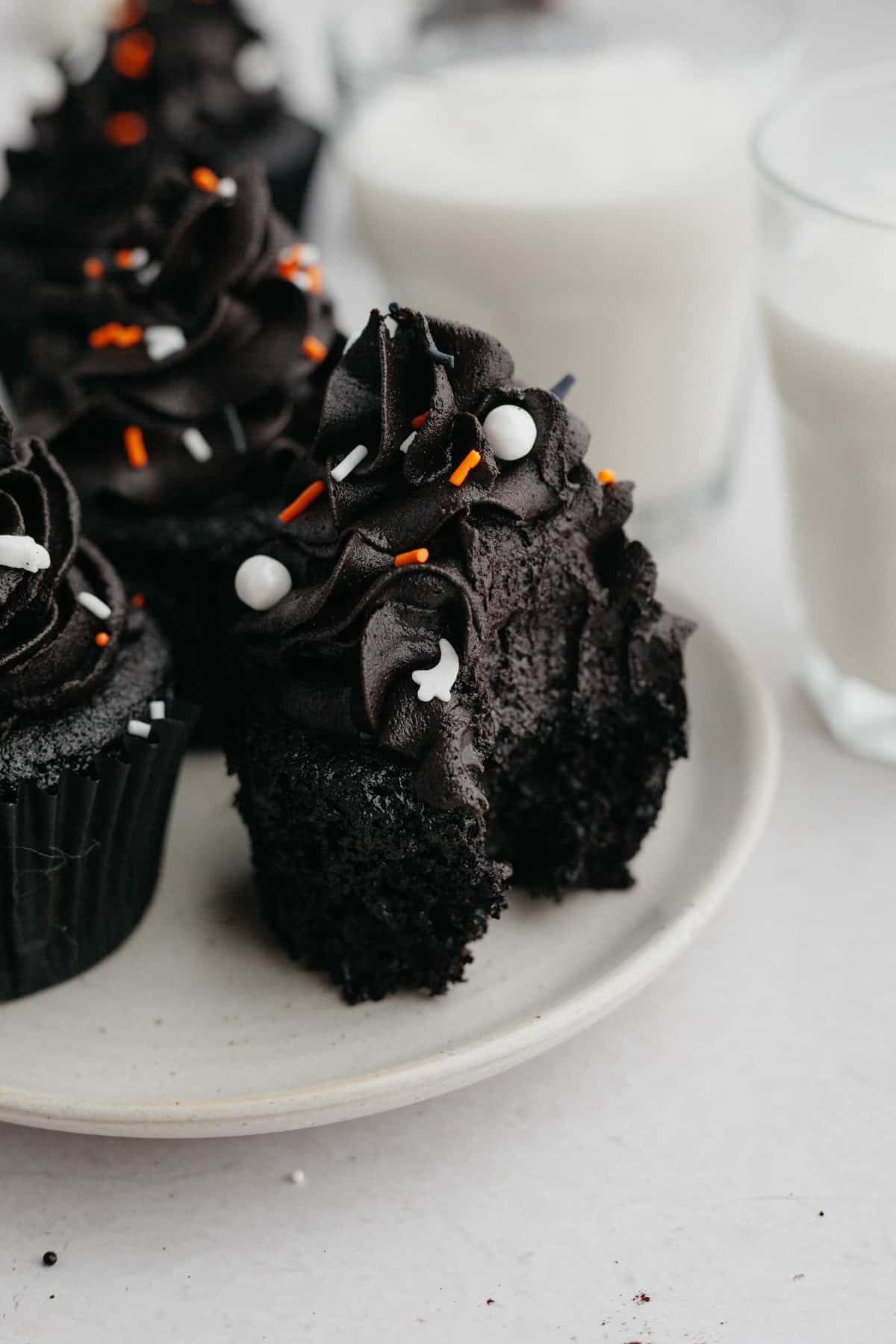 A black velvet cupcake with a bite taken out of it.