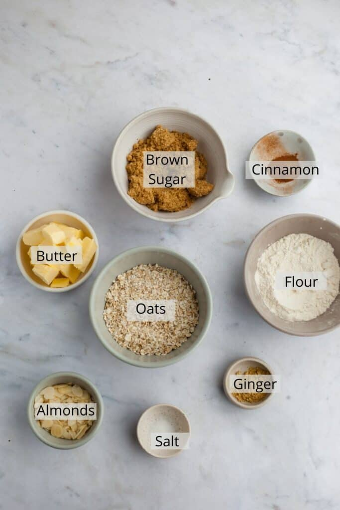 ingredients for ginger oat topping weighed out into small bowls.