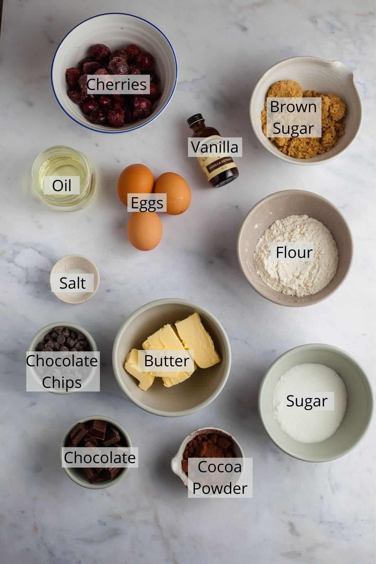 All the ingredients needed for cherry brownies weighed out in small bowls.