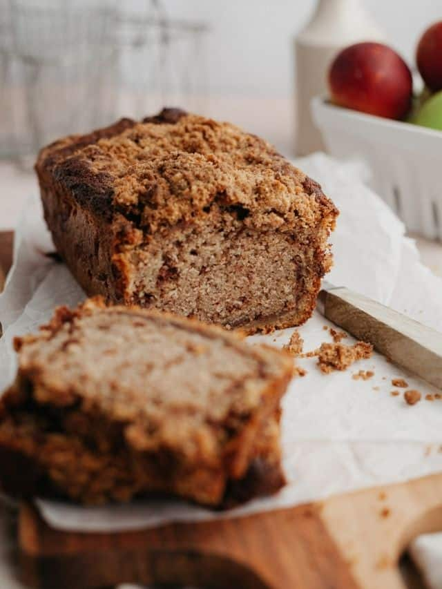 A snickerdoodle apple bread loaf on parchment paper, two slices have been cut off.